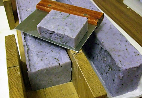 Soap being cut from log mold into bars.